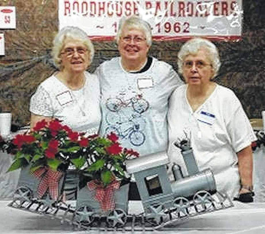 Sisters Skippy Vinyard German (from left), Class of 1949; Dorothy Vinyard Hinegardner, Class of 1960; and Charlotte Vinyard Driver, Class of 1952; attend the 2018 Roodhouse alumni banquet. The train was loaned to the alumni as a centerpiece by Lyndell and Dixie Martin Winters. Photo:       Photo Provided