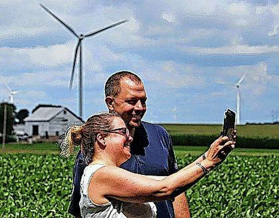 Katie Gillespie and Jim Klempir take a selfie during the E.ON Radford's Run Wind Farm dedication near Maroa. The event marked putting 139 turbines into place stretching into the sky in northwestern Macon County, generating energy for a grid that spans 13 states. Photo:       Jim Bowling | Herald & Review (AP)