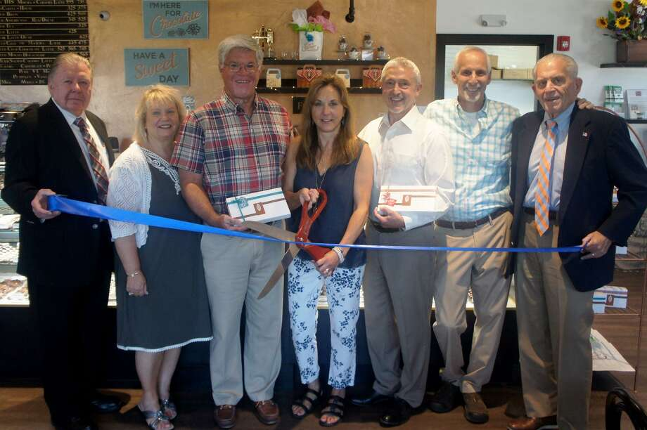 Essex Chocolatier and Coffee Bar held a ribbon cutting July 18 at 124 Westbrook Road. From left are Middlesex County Chamber of Commerce Chairman Jay Polke, Ambassador Sue Anne Podaski, Chester/Deep River/Essex Division Chairman Geoff Jacobson, Essex Chocolatier owners Teresa Patrick-Connell and Mark Connell, First Selectman Norm Needleman and Chamber President Larry McHugh. Photo: Contributed Photo