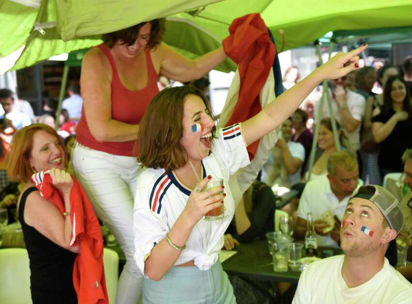 France fans, from left, Florence Chang, of Norwalk, Caroline Menchero, of Norwalk, Andrea Menchero, of Brooklyn, N.Y., and Ryan Graham, of West Hartford, celebrate as time expires in France's 4-2 win over Croatia in the FIFA World Cup final viewing party outside of Capriccio Cafe in Stamford, Conn. Sunday, July 15, 2018. Enthustiastic fans flocked to the bars to watch as France beat Croatia 4-2 to win its second World Cup.
