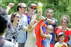 People pose for photos with a replica trophy after they viewed France win over Coatia in the World Cup at a watch party at Discovery Green, 1500 McKinney St., Sunday, July 15, 2018, in Houston.