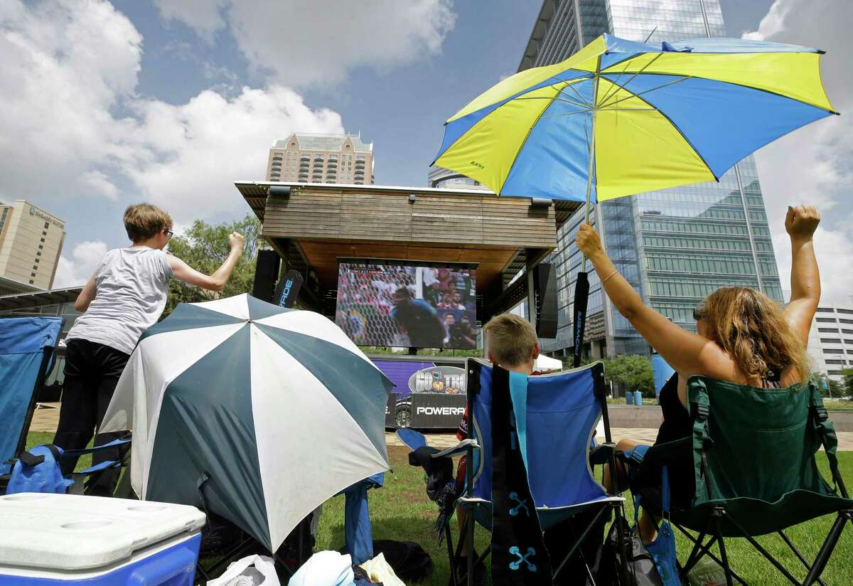 Dylan Dunn, 13, left, John Shelton, 11, center, and John's mother, Regina Shelton, right, cheer the third goal by France as they watch the World Cup at Discovery Green, 1500 McKinney St., Sunday, July 15, 2018, in Houston.