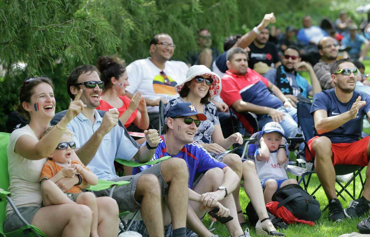 Claire Briane, left, and her husband, Benoit Briane, with their two-year-old son, Anthony Briane, cheer for France among friends gathered at Discovery Green, 1500 McKinney St., to watch the World Cup Sunday, July 15, 2018, in Houston.