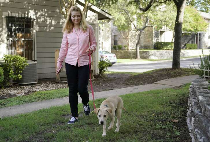 Pfc. Alina Kaliuzhna walks her puppy, Ivy, Tuesday, July 10, 2018, at her home in San Antonio. (Darren Abate/For the Express-News)