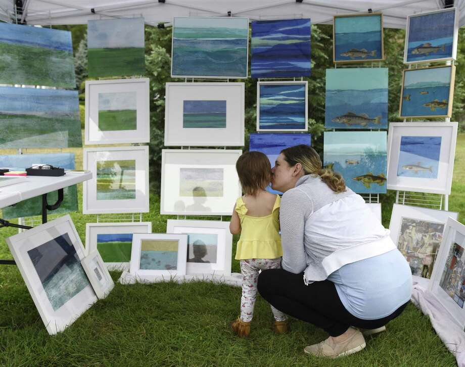 a mother gives her daughter a kiss while looking at work from local artist Melissa Rozmus at the inaugural Old Greenwich Merchants Art in the Park event at Binney Park in Old Greenwich, Conn. Sunday, July 15, 2018. The event featured two dozen local artists exhibiting and selling their work in a variety of mediums, including painting, photography, digital art, ceramics and more. Photo: Tyler Sizemore / Hearst Connecticut Media / Greenwich Time