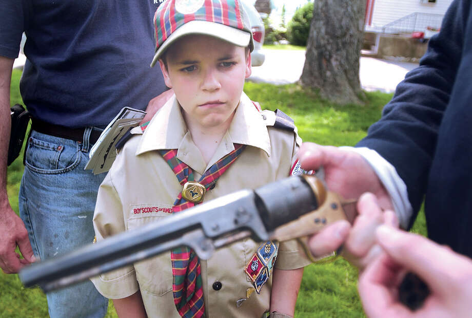 Cub Scout Matt Amendola, 9, looks on as a member of the 2nd Connecticut Volunteer Heavy Artillery Company I explains a Civil War era handgun during the Decoration Day celebration in Durham on Sunday.  The event included a ceremony in the Old Cemetery behind Town Hall honoring the life of Luther and Seymore White, artillary demonstrations, music and more......J. Rossi photo......052304. Photo: Middletown Press File Photo