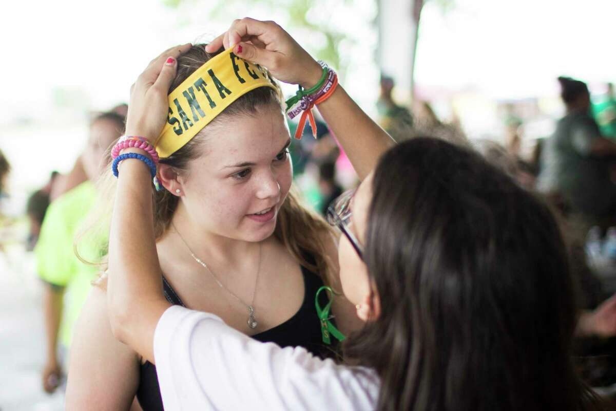 Diona Evers, right, help her friend Sara Reul wear a Santa Fe headband at the Santa Fe High School's class of 2008 reunion fundraising event benefiting the victims of the Santa Fe shooting, Sunday, July 15, 2018.
