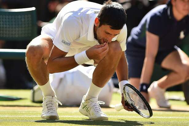 Serbia's Novak Djokovic eats some grass from the court as he celebrates after beating South Africa's Kevin Anderson 6-2, 6-2, 7-6 in their men's singles final match on the thirteenth day of the 2018 Wimbledon Championships at The All England Lawn Tennis Club in Wimbledon, southwest London, on July 15, 2018. / AFP PHOTO / Glyn KIRK / RESTRICTED TO EDITORIAL USEGLYN KIRK/AFP/Getty Images