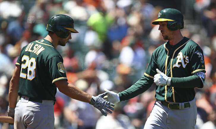 Oakland Athletics' Stephen Piscotty, right, is congratulated by Matt Olson (28) after hitting a home run off San Francisco Giants' Reyes Moronta in the sixth inning of a baseball game Sunday, July 15, 2018, in San Francisco. (AP Photo/Ben Margot)