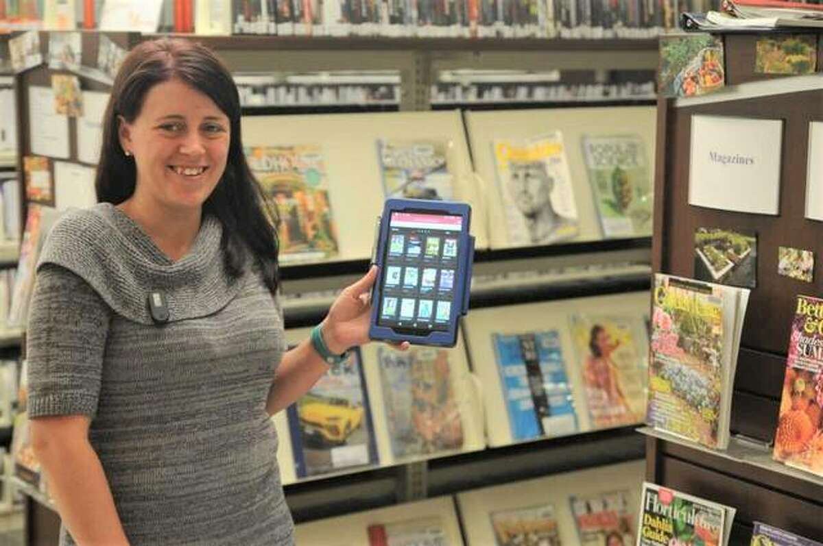 Hayner Public Library assistant Amanda Painter demonstrates the library's new e-magazine service next to the printed magazine section at the library's Alton Square Mall location.