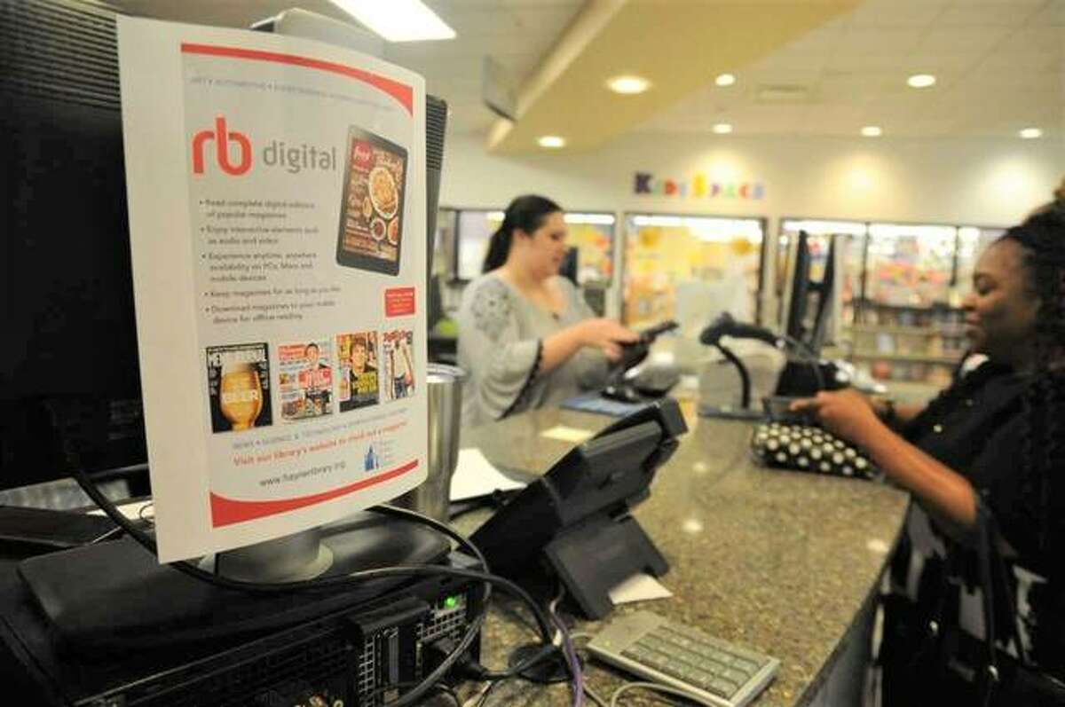 Hayner Public Library assistant Morgan Berry (left) helps patron Sheikera Balentine of Godfrey check items out on Sunday at the library's Alton Square Mall branch. A flier advertising the library's new digital offerings can be seen in the foreground.