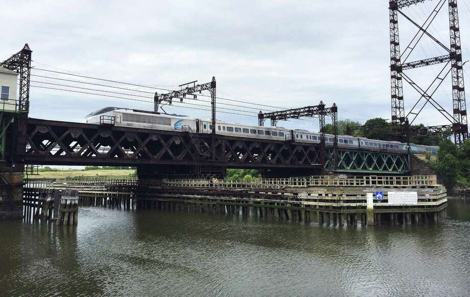 In this June 20 photo, Amtrak's Acela Express crosses the Norwalk River Railroad Bridge, also known as the Walk Bridge, in Norwalk. First built in 1896, it is one of the oldest movable bridges on the Northeast Corridor. The bridge is scheduled to be replaced with a new 240-foot vertical lift bridge beginning in late 2019. A citizens group is challenging the project in federal court raising concerns about the $1.1 billion price tag. Photo: Susan Haigh / Associated Press / Copyright 2018 The Associated Press. All rights reserved.