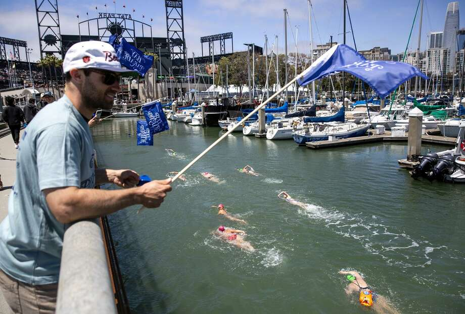 Jake Esmael, a Bay Parade volunteer, encourages swimmers as they arrive at the finish at McCovey Cove. Photo: Photos By Brittany Hosea-Small / Special To The Chronicle / Copyright Brittany Hosea-Small bhoseasmall@gmail.com