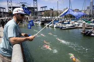 Jake Esmael, a Bay Parade volunteer, encourages swimmers as they arrive at the finish at McCovey Cove.