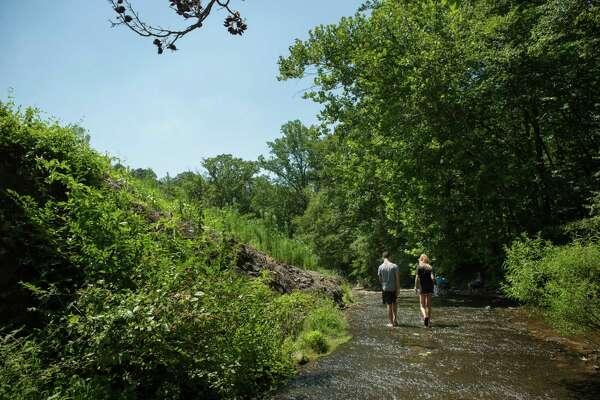 Friends walk through the creek at Capital Camps in Waynesboro, Pa.