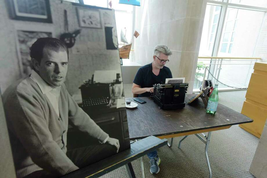 "A photo of a young William Kennedy is seen on display as artist Tim Youd retypes ""Ironweed"" by Kennedy at the Albany Institute of History & Art on Sunday, July 15, 2018, in Albany, N.Y. as part of his 100 Novels Project. For each novel, Youd uses the same make and model typewriter used by the author. He types each novel on a single sheet of paper, which is backed by an additional support sheet. The two-ply paper is loaded through the typewriter repeatedly, until the entire novel has been retyped. Once finished, the two pages are separated and mounted side by side as a framed diptych, recalling two pages of an open book with the words obscured. Youd will be continuing the typing Tuesday Through Saturday. Thursday evening from 6:00pm to 7:45pm there will be a special tasting on the museum grounds of Albany Distilling Company's Ironweed line.  (Paul Buckowski/Times Union) Photo: Paul Buckowski / (Paul Buckowski/Times Union)"