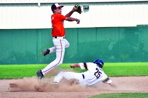 Edwardsville shortstop Logan Cromer, left, leaps over a runner near second base to try to complete a double play during tournament action on Sunday inside Tom Pile Field.