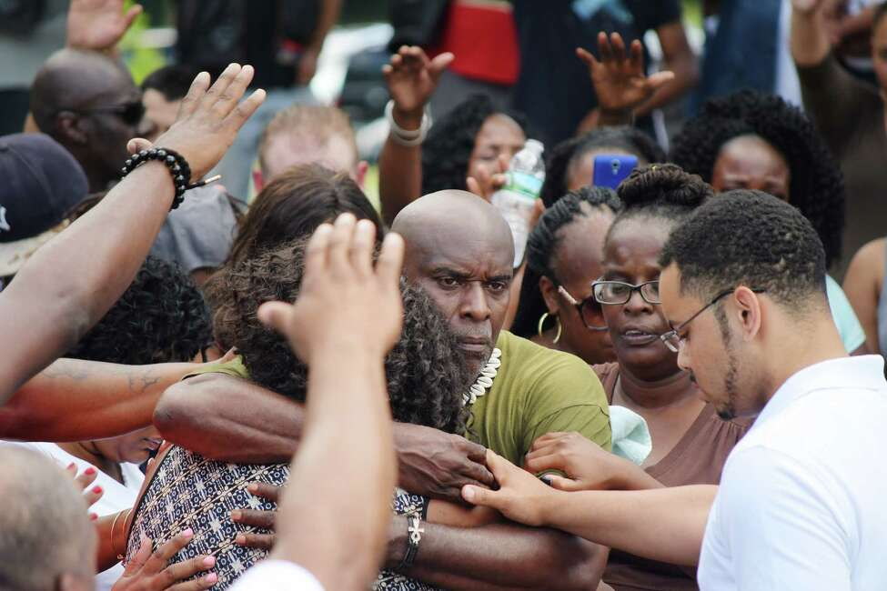 The mother of Khalil Barnes, Fatima Rucker, left, and his father, Justice Barnes, embrace each other as community members pray around them during a community meeting at Arbor Hill Park on Sunday, July 15, 2018, in Albany, N.Y. Khalil Barnes was killed early Saturday morning in Albany. (Paul Buckowski/Times Union)