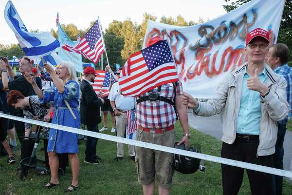 Supporters of US President Donald Trump hold an US flag as the Presidential motorcade passes by in Helsinki, Finland on July 15, 2018, on the eve of the meeting between the US President and his Russian counterpart. / AFP PHOTO / Alessandro RAMPAZZOALESSANDRO RAMPAZZO/AFP/Getty Images