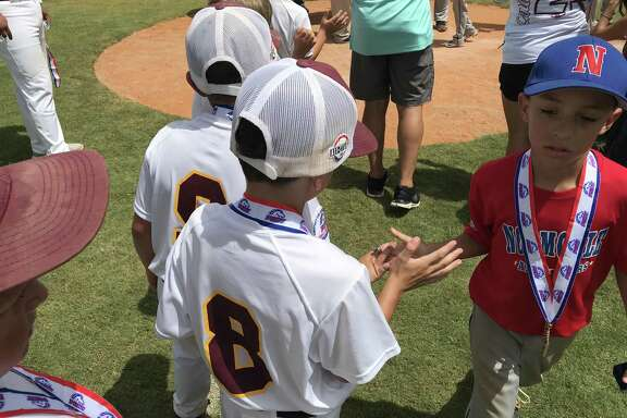 A Normoyle player goes down the line of Deer Park players during postgame ceremonies at the Pinto 7U world series Sunday afternoon.