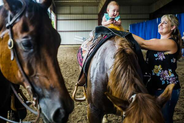 Katie Rose holds onto her daughter, Gwendalyn Rose, 5 months, while she sits on the back of a horse after they watched a friend compete in a Michigan Reining Horse Association competition on Saturday, July 14, 2018 at the Midland County Fairgrounds. (Katy Kildee/kkildee@mdn.net)