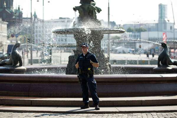 A police officer stands guard by a water fountain close to the Presidential Palace in Helsinki, Finland, on July 16, 2018.