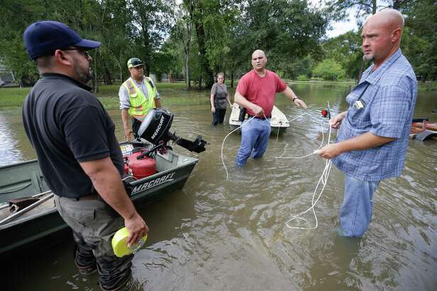Robert Spooner, a US Customs and Border patrol officer, from Tomball, center, and other volunteers work to prepare boats to help people in the Lakewood area along Cypresswood. First responders and county officials are readying for the hurricane season in northwest Harris County.