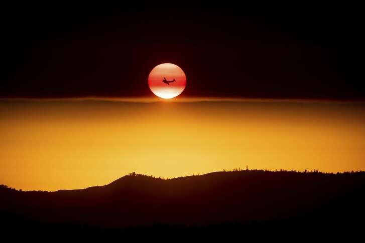 A plane battling the Ferguson Fire passes the setting sun in unincorporated Mariposa County Calif., near Yosemite National Park on Sunday, July 15, 2018. (AP Photo/Noah Berger)