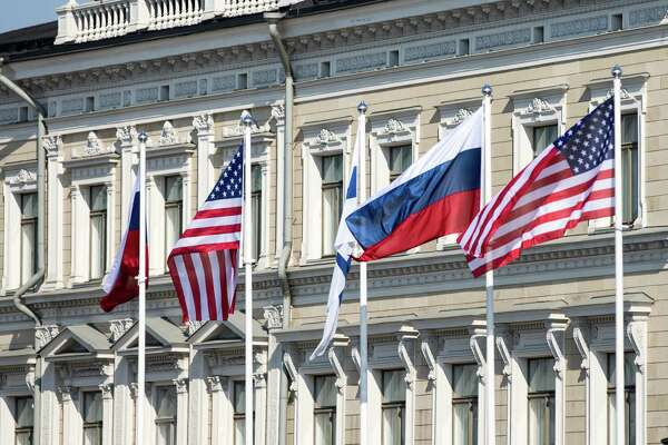 Russian national flags, American national flags, and a Finnish national flag fly outside the Presidential Palace in Helsinki, Finland, on July 16, 2018.