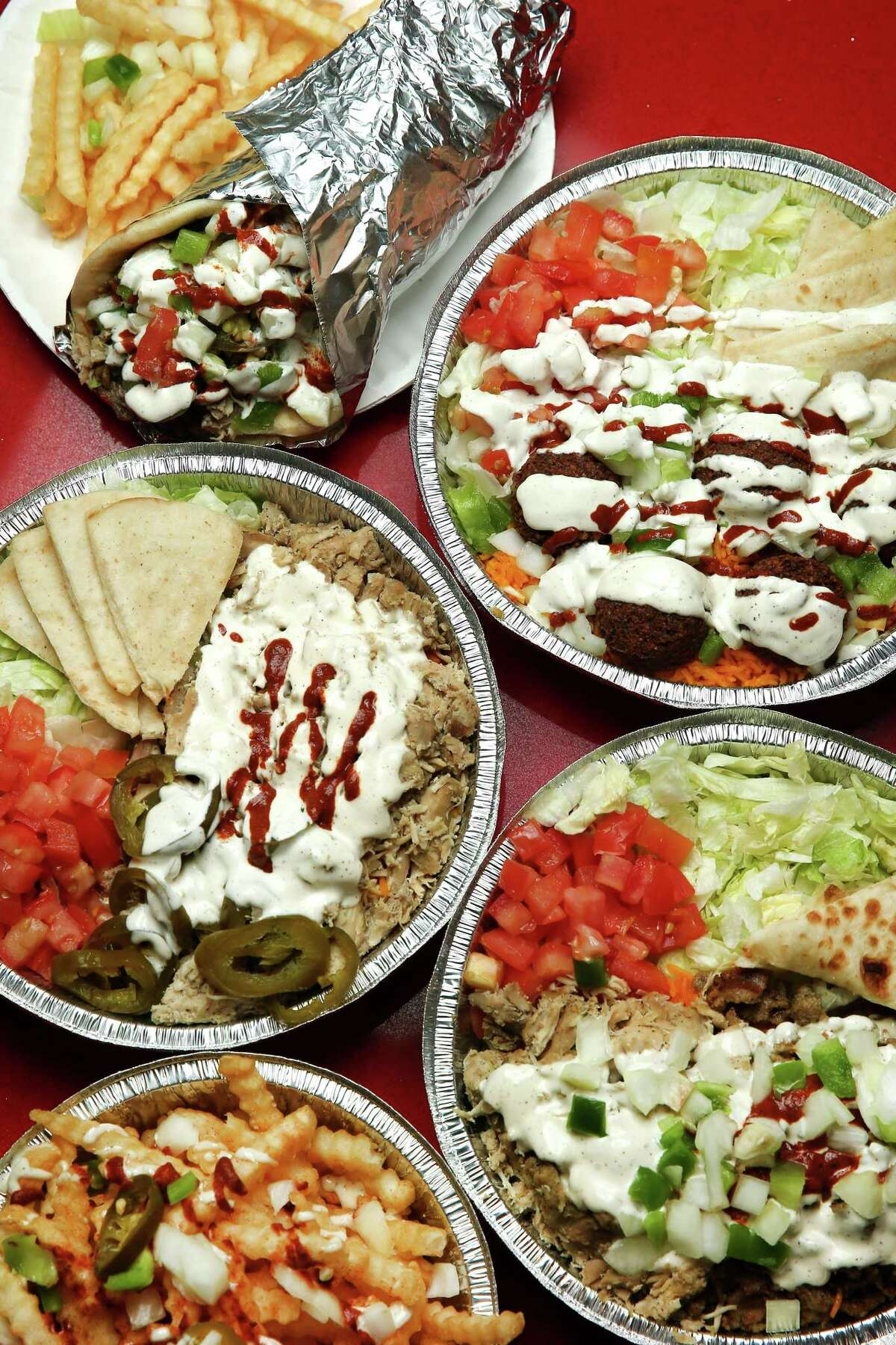 The chicken sandwich with fries; gyro and falafel combo platter; chicken platter with jalapenos; combo platter; and a side of fries at The Halal Guys.