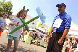 Augusta Wartels, 7, of Darien, gets a flower from The Great Scirico of Milford, at the annual New Canaan Chamber of Commerce Village Fair and Sidewalk Sale, downtown on Saturday, July 14, 2018, in New Canaan, Conn.