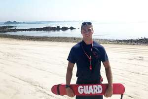 Lifeguard Morgan Carson saved three fishermen who had capsized their canoe off his beach at the Woodway Beach Club on Westcott Cove in Stamford on Saturday July 14, 2018