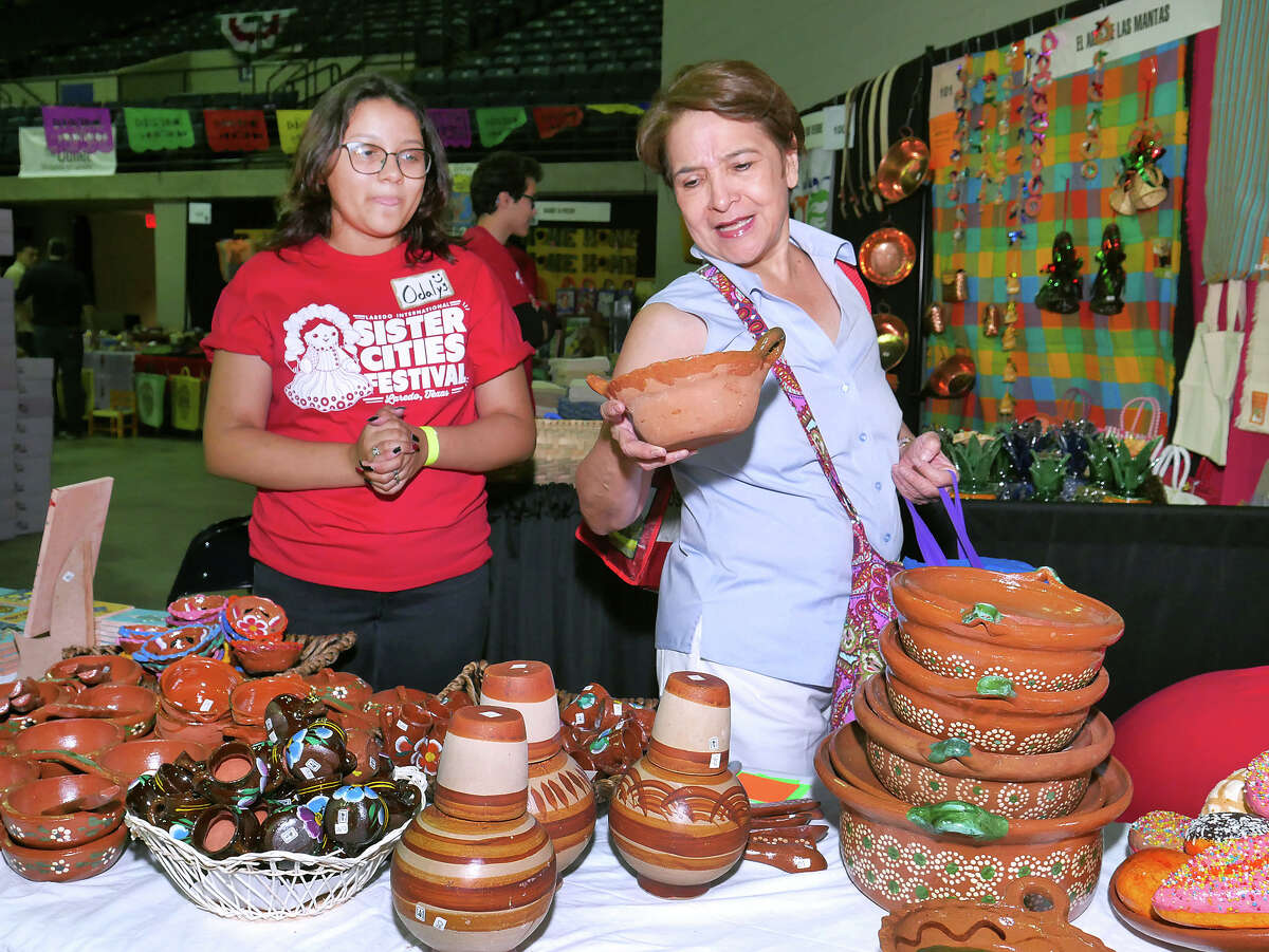 Carmen Escamilla gets help from Odalys Grajeda as she shops for Mexican pottery at the 16th Annual Laredo International Sister Cities Festival, Friday, July 13, 2018 at the Sames Auto Arena. There will be arts and crafts, leather goods, jewelry, pottery, food, music, clothing and folkloric dances and presentations at the event free event through Sunday.