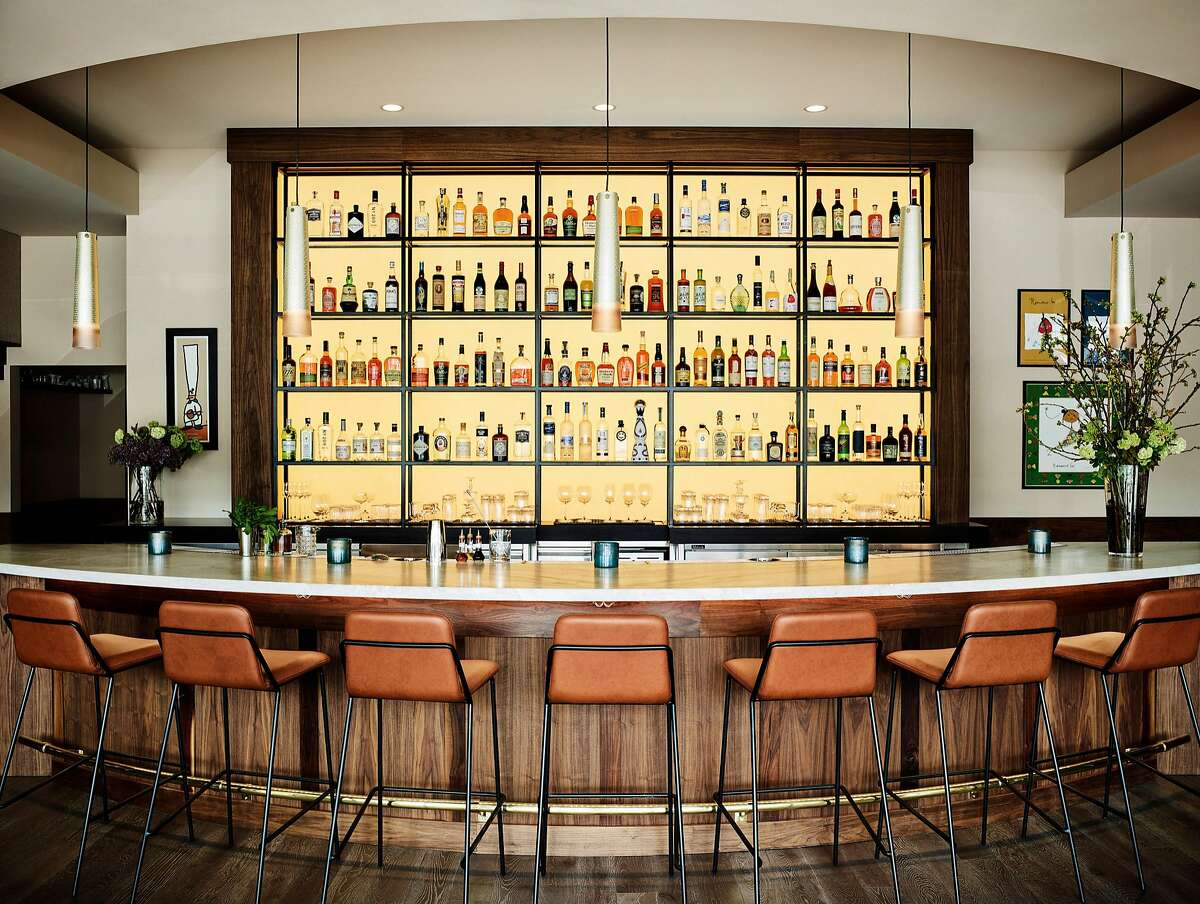 At Protege restaurant in Palo Alto, the first thing diners see is the bar, lit from behind and done in curvilinear fashion to be more inviting and less stark than a bar with straight lines. Bar stools are made of caramel-colored leather.
