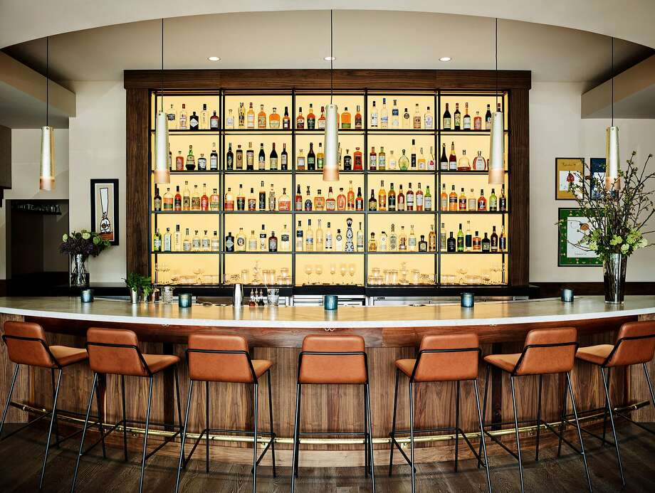 At Protégé restaurant in Palo Alto, the first thing diners see is the bar, lit from behind and done in curvilinear fashion to be more inviting and less stark than a bar with straight lines. Bar stools are made of caramel-colored leather. Photo: Douglas Friedman