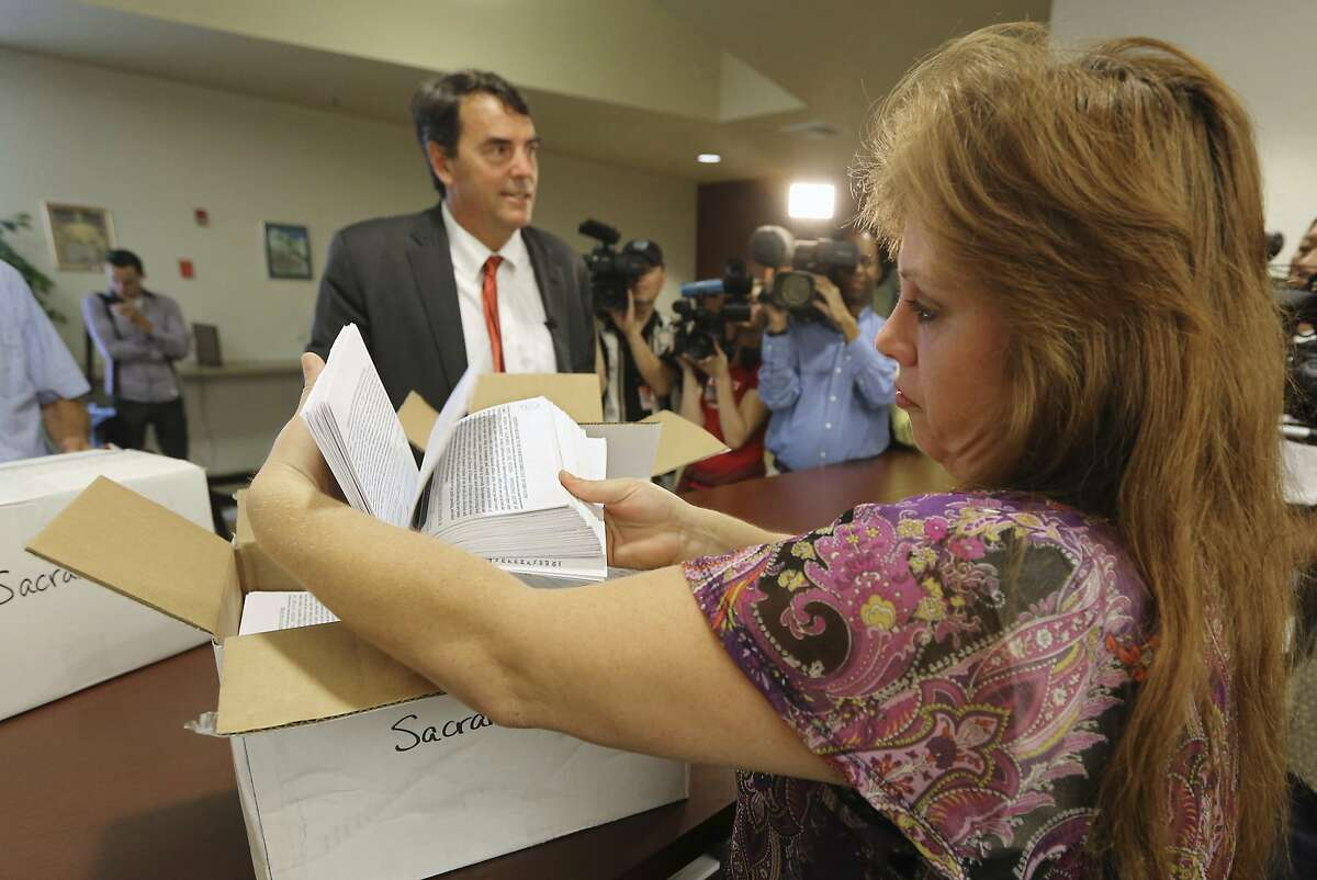 An elections manager for the Sacramento County Registrar of Voters makes a quick inspection of some of the petitions turned in by Silicon Valley venture capitalist Tim Draper, left, that would place a ballot initiative before voters asking to split California into separate states.