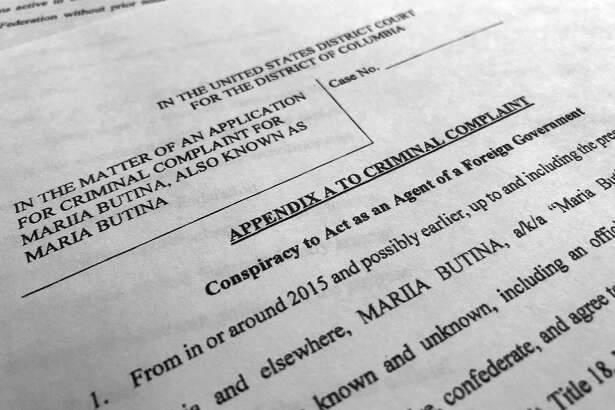 Court papers unsealed Monday, July 16, 2018, photographed in Washington, shows part of the criminal complaint against Maria Butina. She was arrested July 15, on a charge of conspiracy to act as an unregistered agent of the Russian government. (AP Photo/Jon Elswick