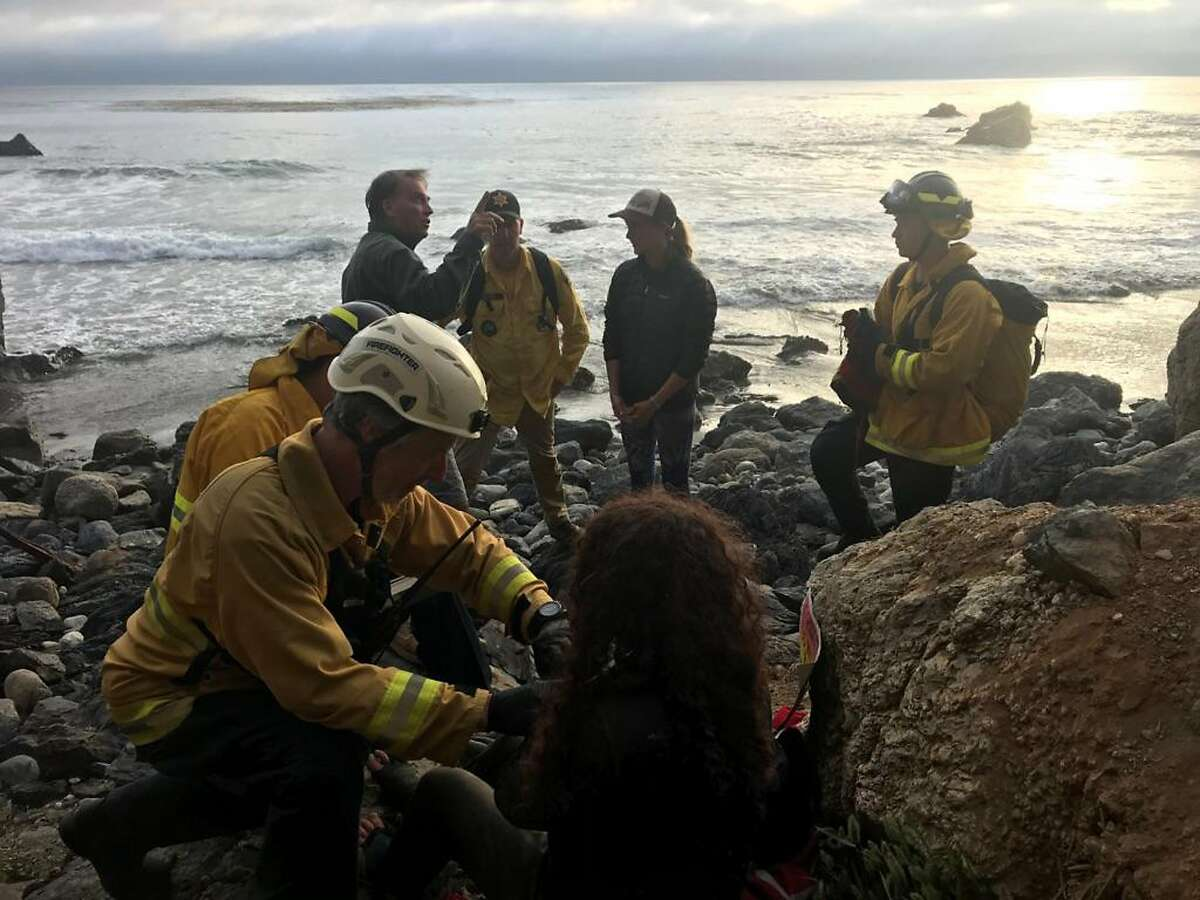 In this Friday, July 13, 2018, photo posted on the Monterey County, Calif., Sheriff's Office Twitter feed, authorities tend to Angela Hernandez, foreground center, after she was rescued, in Morro Bay, Calif. Authorities say a couple on a camping trip came upon Hernandez, from Oregon, who had been missing since July 6, after her car went over a cliff in coastal California.