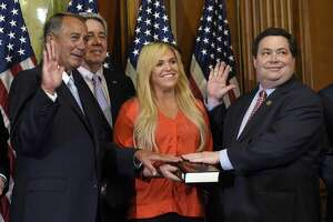 House Speaker John Boehner of Ohio poses for a photo with Rep. Blake Farenthold, R-Texas, right, accompanied by family, to re-enact the House oath-of-office, Tuesday, Jan. 6, 2015, on Capitol Hill in Washington. (AP Photo/Susan Walsh)