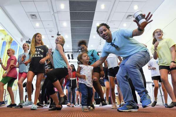 Program Director Luis Salgado, second from right, helps two-year-old Amina Boyd, center, lead a group of performers attending the Palace Theatre ArtsKids Summer Camps program on July 13, 2018 in Stamford, Connecticut.