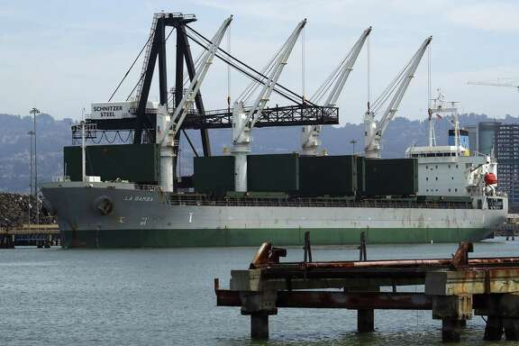A ship is loaded with scrap metal by Schnitzer Steel at the Port of Oakland Thursday, July 12, 2018, in Oakland, Calif. The United States has imposed tariffs of 25 percent on steel and 10 percent on aluminum on the grounds that the imported metals pose a threat to U.S. national security. China, the EU, Canada, Mexico and Turkey have counterpunched with taxes on more than $24 billion worth of U.S. exports.