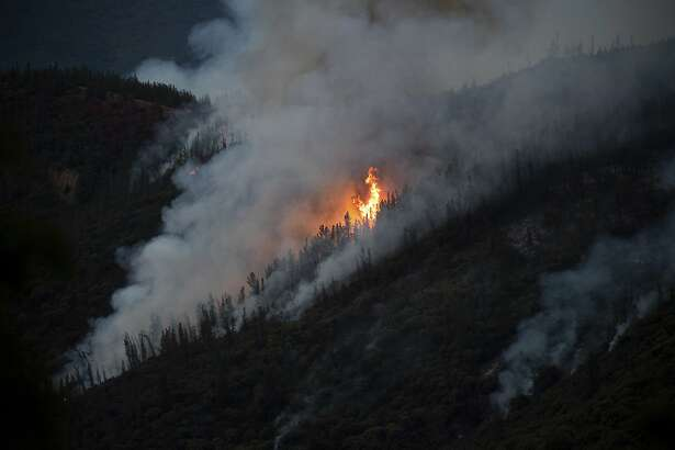 Flames from the Ferguson Fire burn down a hillside in unincorporated Mariposa County Calif., near Yosemite National Park on Sunday, July 15, 2018. (AP Photo/Noah Berger)
