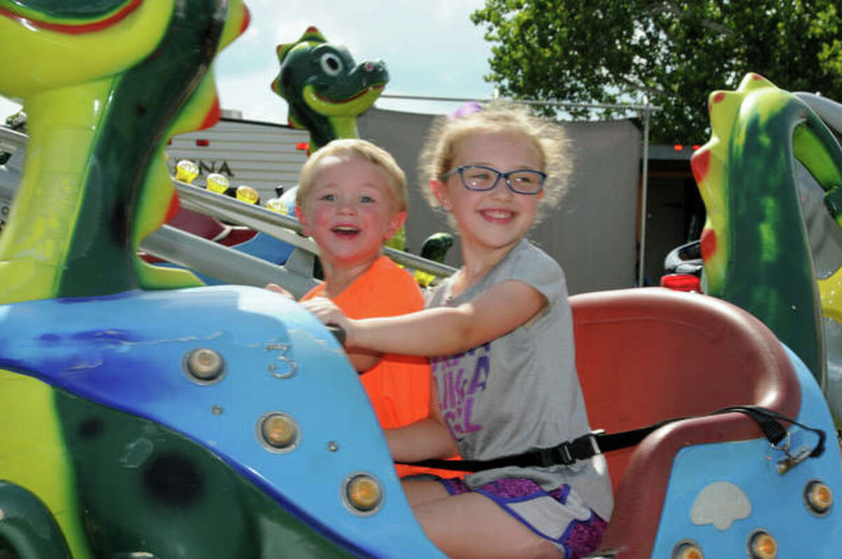 Two-year-old Talan Steinacher of Carrollton and his six-year-old sister Brooklyn whiz by on a carnival ride Sunday at the Jersey County Fair.
