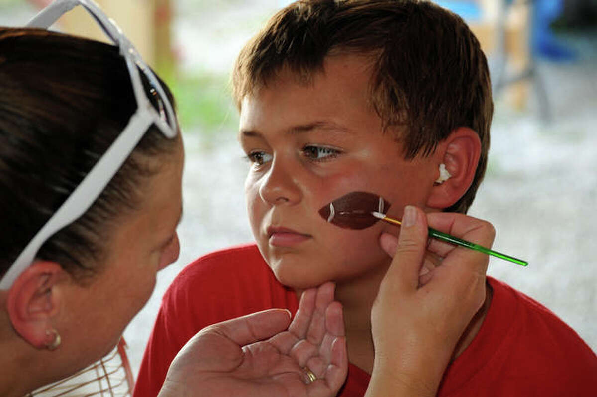 Joan Roach of The Crafty Chicks adds facial art to customer Brody Short, 9, of Jerseyville on Sunday.