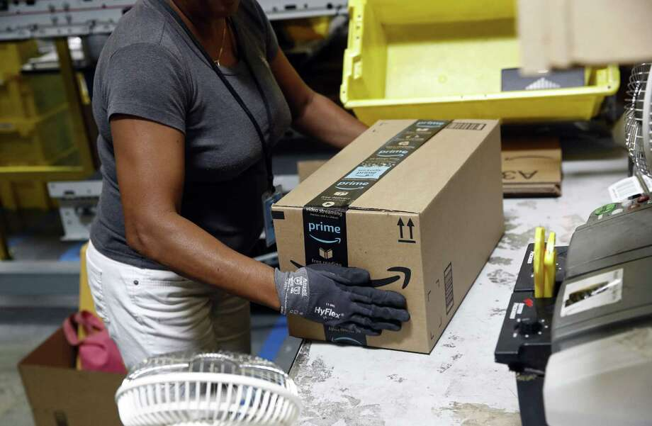 In this Aug. 3, 2017, photo, Myrtice Harris applies tape to a package before shipment at an Amazon fulfillment center in Baltimore. Amazon's Prime Day starts July 16, 2018, and will be six hours longer than last year's and will launch new products. Photo: Patrick Semansky /Associated Press / Copyright 2017 The Associated Press. All rights reserved.