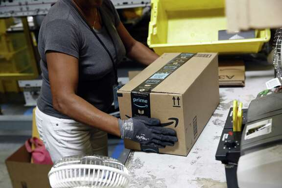 In this Aug. 3, 2017, photo, Myrtice Harris applies tape to a package before shipment at an Amazon fulfillment center in Baltimore. Amazon's Prime Day starts July 16, 2018, and will be six hours longer than last year's and will launch new products.