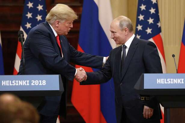 U.S. President Donald Trump, left, shakes hands with Vladimir Putin, Russia's president, during a news conference in Helsinki, Finland, on Monday.