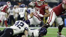 TCU linebacker Ty Summers (42) and safety Ridwan Issahaku (31) combine to stop Oklahoma running back Rodney Anderson (24) after a short run in the second half of the Big 12 Conference championship NCAA college football game, Saturday, Dec. 2, 2017, in Arlington, Texas. (AP Photo/Tony Gutierrez)