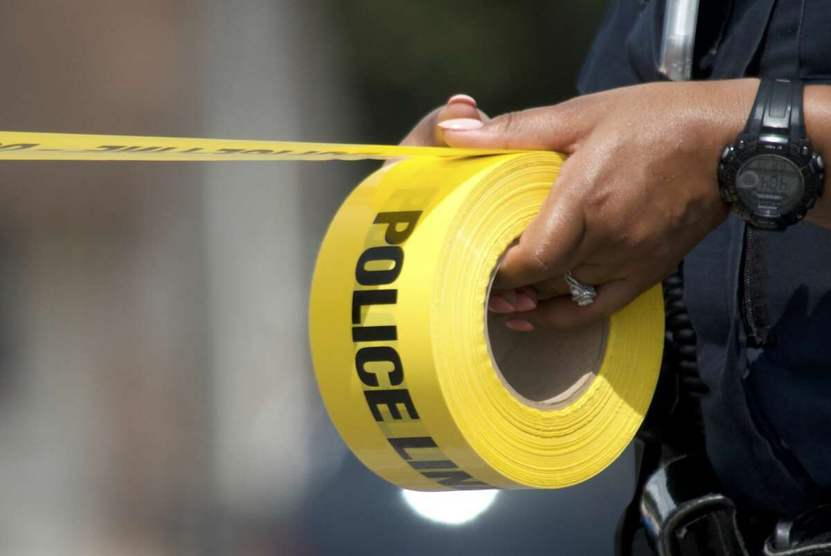A Houston police officer unravels police tape Friday, July 13, 2018.
