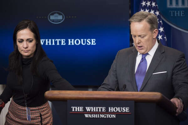Stephanie Grisham, now communications director for the office of the first lady, hands former White House press secretary Sean Spicer a note as he speaks during the daily news briefing at the White House on Jan. 30, 2017.